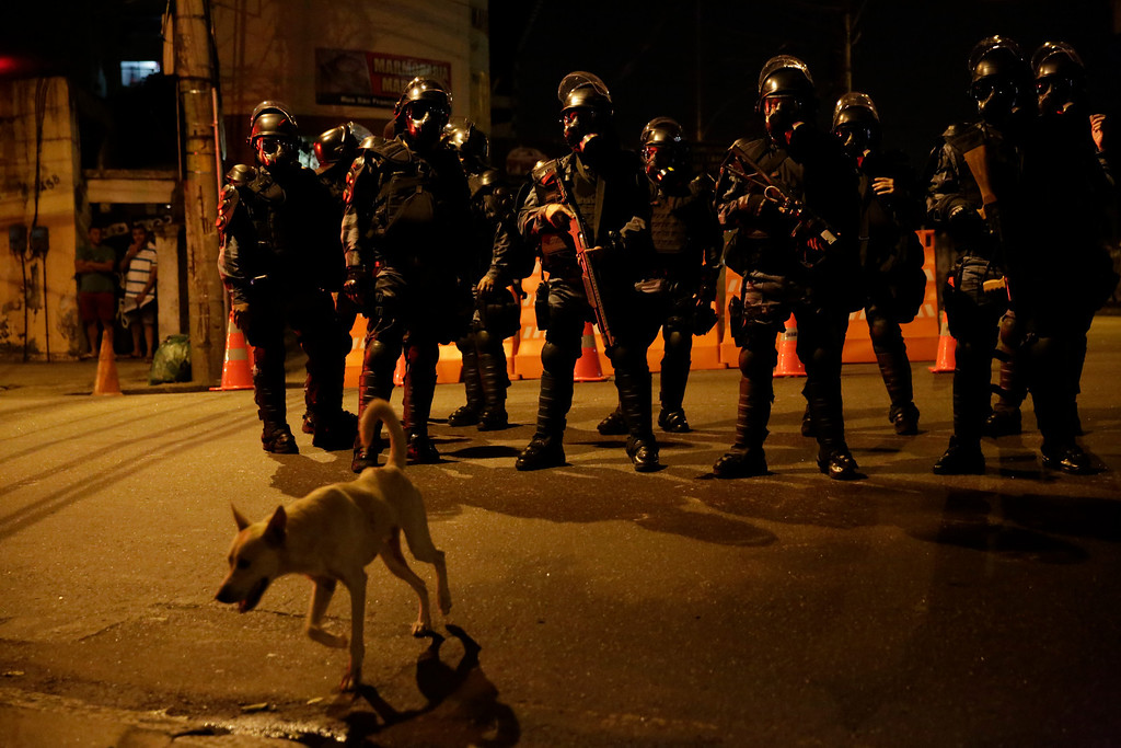 . A dog passes heavily equipped police outside Maracana Stadium during the World Cup soccer match between Argentina and Bosnia in Rio de Janeiro, Brazil, Sunday, June 15, 2014.  Anti-World Cup protesters demonstrated near the stadium.  (AP Photo/Matt Dunham)
