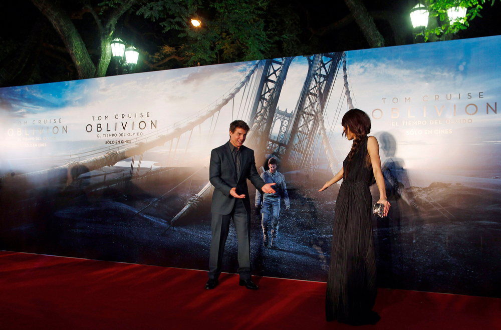 ". U.S. actor Tom Cruise gestures to Ukrainian-born actress Olga Kurylenko (R) on the red carpet before the world premiere of their movie ""Oblivion\"" in Buenos Aires March 26, 2013. REUTERS/Marcos Brindicci"