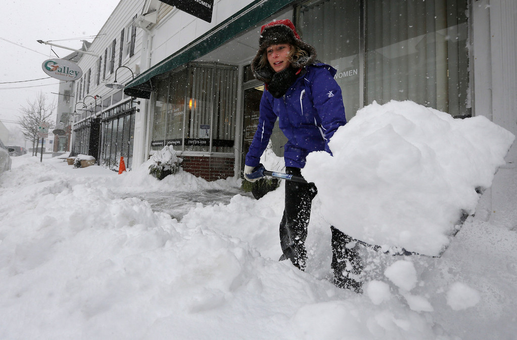 . Alisa Riley, of Hingham, Mass., shovels snow from a sidewalk in front of a women\'s fitness center where she works in Scituate, Mass., Wednesday, Jan. 22, 2014. The National Weather service reports that by Wednesday morning some towns in the state had about 18 inches of snow from a winter storm. (AP Photo/Steven Senne)