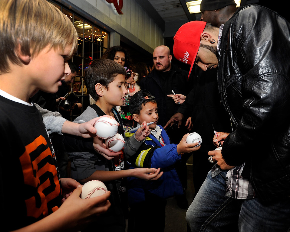 . Giants reliever Sergio Romo, right, signs autographs for young fans at a Marine Corps Reserve Toys For Tots event at Kinder\'s Meat and Deli on Wednesday, Dec. 12,  2012, in Pleasant Hill, Calif.  (Susan Tripp Pollard/Staff)