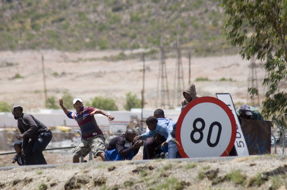 . Striking farmworkers and other protestors throw stones, while hiding behind broken road signs during violent clashes with members of the South African Police Services(not visible), on January 10, 2012 in de Doorns, a small farming town about 140Km North of Cape Town, South Africa. The farm workers have said that they they will not return to work on the fruit growing region\'s farms until they receive a daily wage of at least R150($17) per day, which is about double what they currently earn. AFP / RODGER  BOSCH/AFP/Getty Images