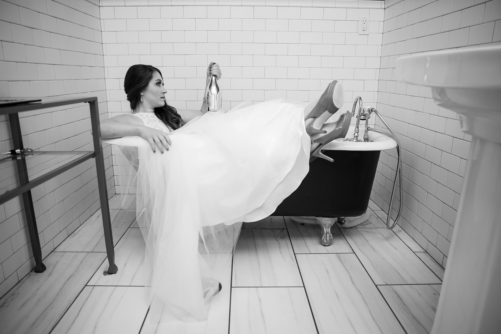 black and white photo of a bride in a bathtub holding a bottle of wine