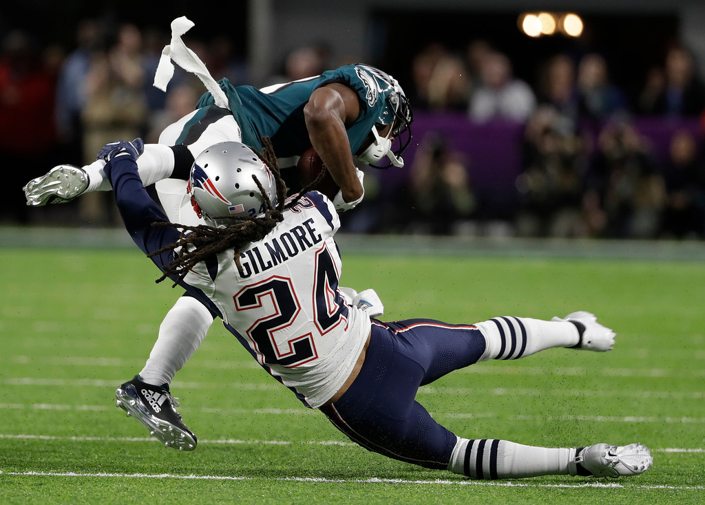 . New England Patriots cornerback Stephon Gilmore (24), tackles Philadelphia Eagles wide receiver Nelson Agholor (13), during the first half of the NFL Super Bowl 52 football game, Sunday, Feb. 4, 2018, in Minneapolis. (AP Photo/Chris O\'Meara)