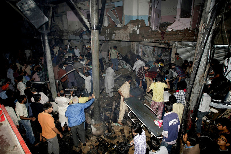 . Pakistani medics and civilians gather at the site of a bomb blast in Karachi, Pakistan, Sunday, March 3, 2013. Pakistani officials say a bomb blast has killed dozens of people in a neighborhood dominated by Shiite Muslims in the southern city of Karachi. (AP Photo/Fareed Khan)