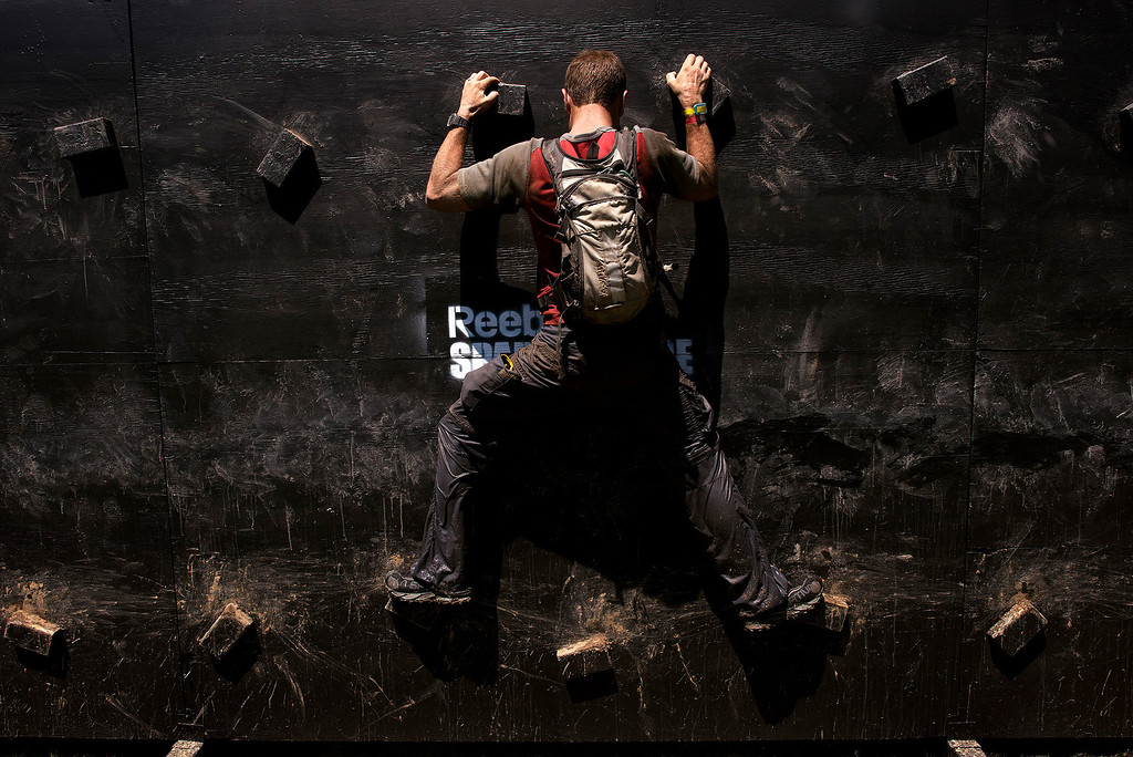 . A racer clings to a traverse wall Saturday, August 10th, 2013 during the first annual Monterey Spartan Race at Toro Park. (Matthew Hintz/Monterey County Herald)