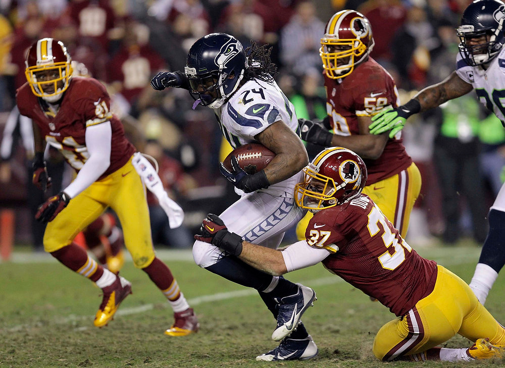 Description of . Seattle Seahawks running back Marshawn Lynch (24) is tackled by Washington Redskins strong safety Reed Doughty (37) in the second half during their NFL NFC wildcard playoff football game in Landover, Maryland, January 6, 2013. REUTERS/Laurence Kesterson