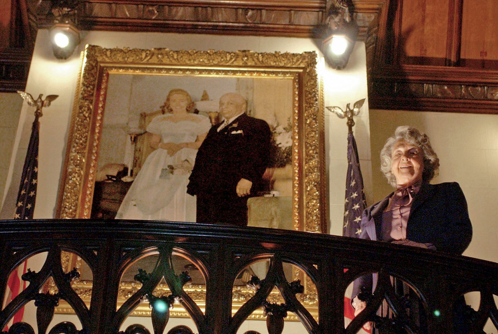 . FILE � In this May 21, 2003, file photo, Mother Divine looks down from a stairwell while standing near a portrait of herself and her late husband Father Divine at her home at Woodmont in Gladwyne, Pa. Mother Divine, the leader for decades of the religious movement Father Divine founded that advocated racial equality and provided free food to thousands of people, died Saturday, March 4, 2017, at the movement\'s Gladwyne estate, according to the Emil J. Ciavarelli Family Funeral Homes. She was believed to be 92. (AP Photo/Jacqueline Larma, File)