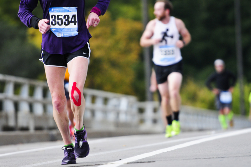 . Donna Philippot of Minneapolis crosses the Franklin Avenue Bridge at the 19-mile mark wearing compression tape on her left knee. (Pioneer Press: Simon Guerra)
