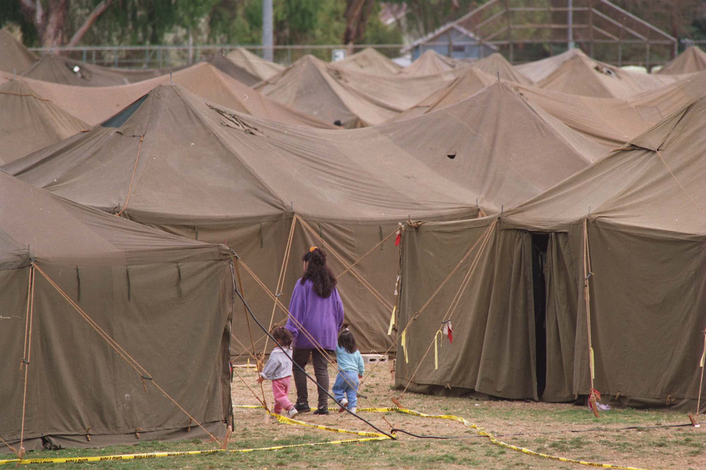 ". A woman leads two children through a maze of tents set up by the National Guard for displaced quake victims at Lanark Park.  The Northridge quake hit at 4:31 the morning of Jan. 17, 1994, a powerful jolt that flattened buildings, destroyed homes, damaged freeways, ignited fires and disrupted water and power.  The 6.7-magnitude Northridge Earthquake also killed nearly three dozen people, injured 8,700 more, caused some $20 billion in damage and shattered the nerves of millions of Southern California residents.  ""It was like the devil was waking up ... it was a horrifying feeling,\"" said one of the quake victims quoted in a Daily News story on Jan. 18. 