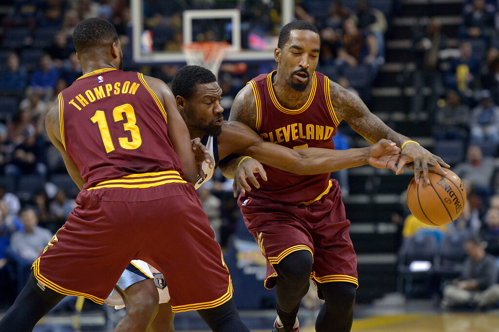 . Memphis Grizzlies guard Tony Allen, center, reaches between Cleveland Cavaliers center Tristan Thompson (13) and guard J.R. Smith, right, to knock the ball loose in the first half of an NBA basketball game Wednesday, Dec. 14, 2016, in Memphis, Tenn. (AP Photo/Brandon Dill)