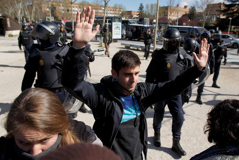 . Riot police remove protesters outside an area near the campus building where some students were arrested during a protest against the government\'s education reforms and cutbacks in university grants and staffing in Campus Ciudad Universitaria on March 26, 2014 in Madrid, Spain. The students began occupying a campus building at Ciudad Universitaria several days ago in protest against the governments\' cuts. Today, they were removed from the premises by police, who made fifty arrests, after the University requested their assistance.  (Photo by Pablo Blazquez Dominguez/Getty Images)