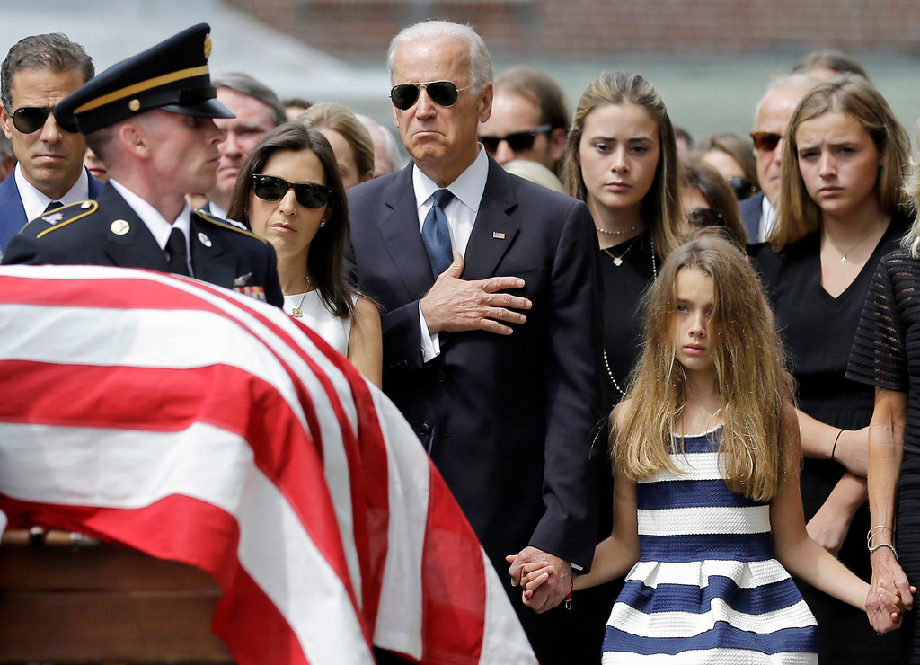 . Vice President Joe Biden, accompanied by his family, holds his hand over his heart as he watches an honor guard carry a casket containing the remains of his son, former Delaware Attorney General Beau Biden, into St. Anthony of Padua Roman Catholic Church in Wilmington, Del., Saturday, June 6, 2015, for funeral services. Standing alongside the vice president are Beau\'s widow Hallie Biden, left, and daughter, Natalie. Beau Biden died of brain cancer May 30 at age 46. (AP Photo/Patrick Semansky)
