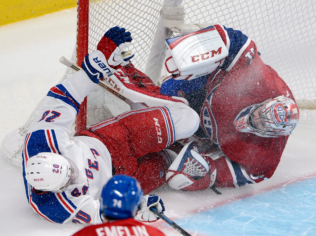 . New York Rangers left wing Chris Kreider (20) crashes into Montreal Canadiens goalie Carey Price, right, during the second period in Game 1 of the Eastern Conference finals in the NHL hockey Stanley Cup playoffs against in Montreal on Saturday, May 17, 2014. (AP Photo/The Canadian Press, Adrian Wyld)