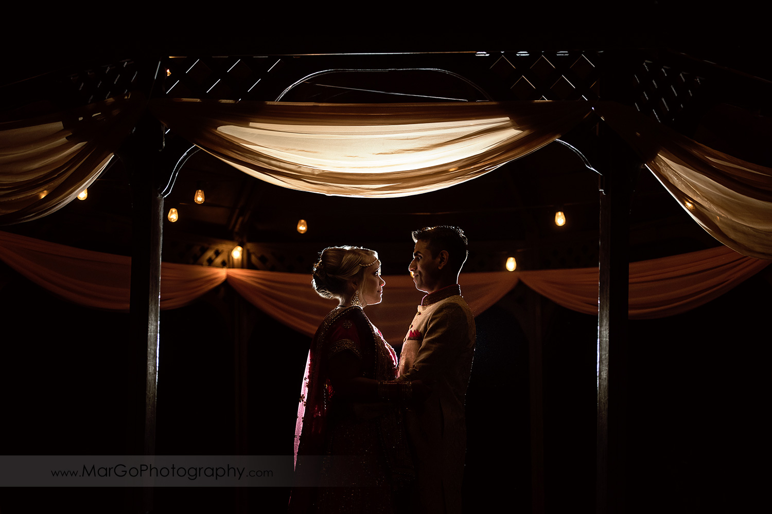 night shot of Indian bride and groom under gazebo at Elliston Vineyards in Sunol
