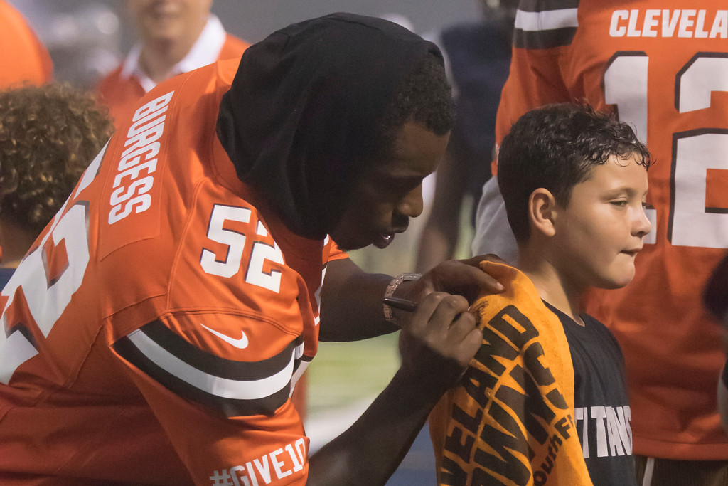. Jen Forbus - The Morning Journal<br> Cleveland Browns linebacker James Burgess signs a towel for a young fan during Lorain\'s game against St. Joseph on Sept. 14.