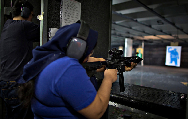 . A woman fires a .22 calibre AR-15 rifle on the range at DVC Indoor Shooting Centre in Port Coquitlam, British Columbia March 22, 2013. The DVC is the only indoor shooting centre in the province that rents firearms to the public without a license. Canada has very strict laws controlling the use of handguns and violent crime is relatively rare. Picture taken March 22, 2013.  REUTERS/Andy Clark