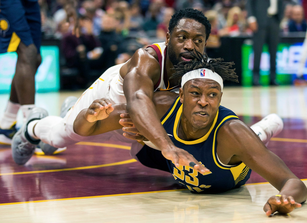 . Cleveland Cavaliers\' Dwyane Wade, left, falls on Indiana Pacers\' Myles Turner while battling for a loose ball during the first quarter of an NBA preseason basketball game, Friday, Oct. 6, 2017, in Cleveland. (AP Photo/Scott R. Galvin)