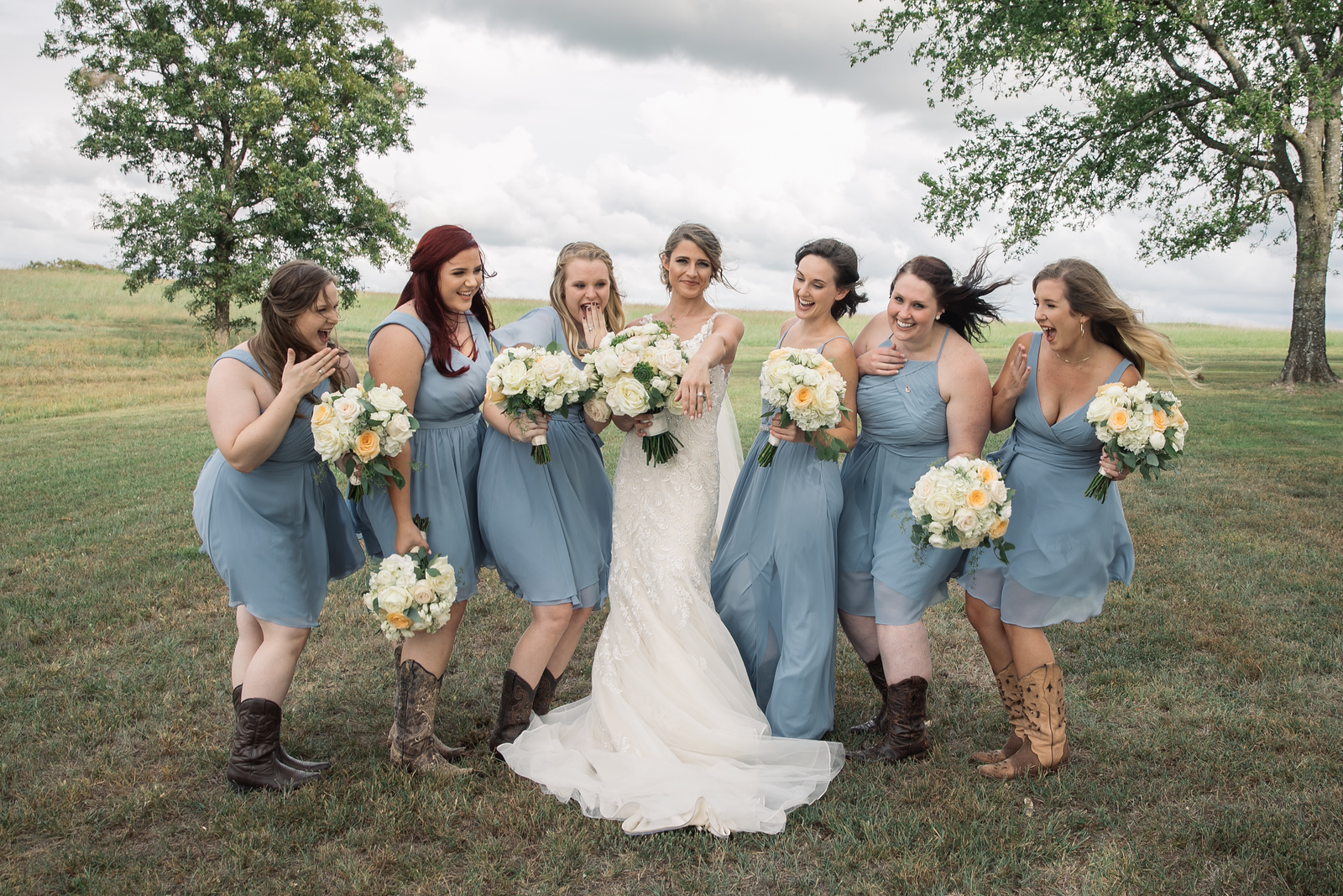 a group of bridesmaids looking at a bride's engagement ring
