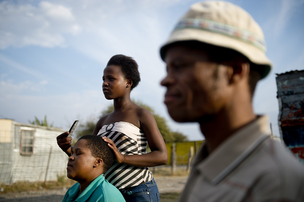 . A woman has her hair trimmed at an outdoor hairdresser on July 9, 2013 in the Nkaneng shantytown next to the platinum mine, run by British company Lonmin, in Marikana. On August 16, 2012, police at the Marikana mine open fire on striking workers, killing 34 and injuring 78, during a strike was for better wages and living conditions. Miners still live in dire conditions despite a small wage increase.  ODD ANDERSEN/AFP/Getty Images
