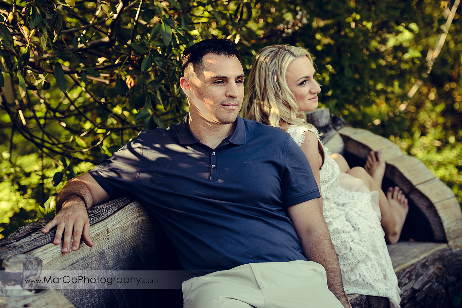 portrait of man in navy blue shirt and woman in white dress sitting back to back during engagement session at San Francisco Golden Gate Park