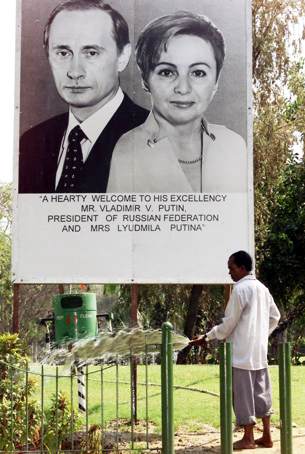. A gardener waters grass in front of a poster of Russian President Vladimir Putin and his wife in New Delhi in this October 2, 2000 photo. Putin and his wife, Lyudmila, said on state television on Thursday that they had separated and their marriage was over after 30 years.  REUTERS/Stringer/Files