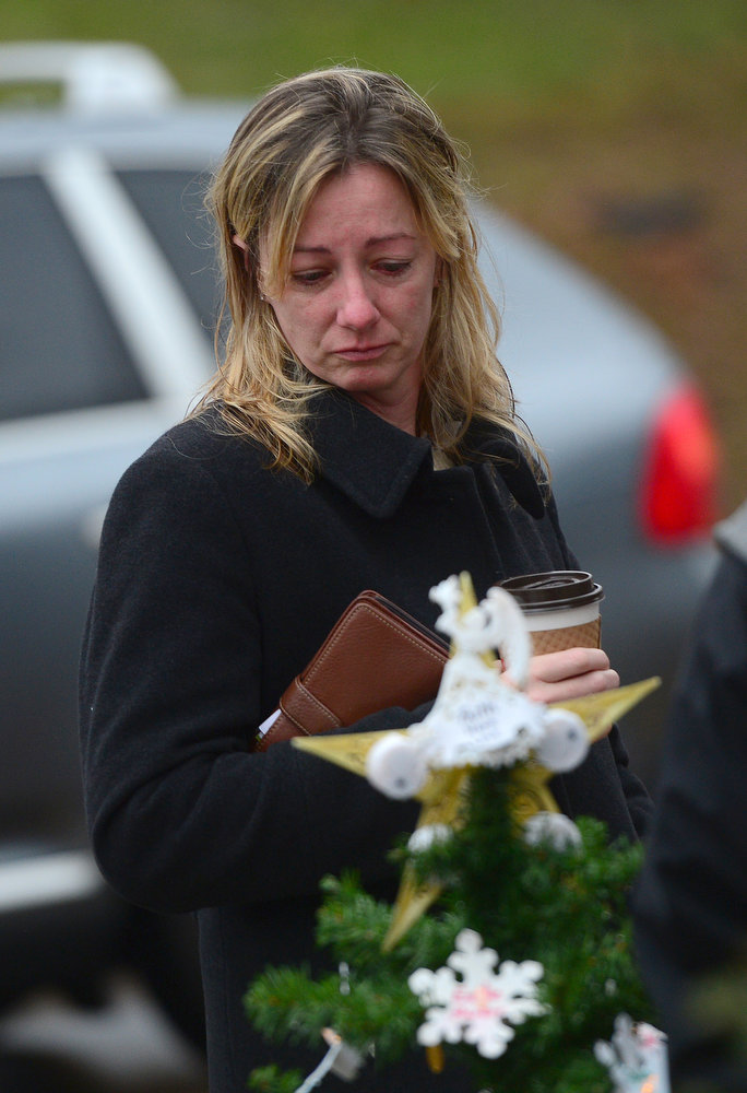 . People pay their respects at a makeshift shrine to the victims of an elementary school shooting in Newtown, Connecticut, December 17, 2012.  Funerals began Monday in the little Connecticut town of Newtown after the school massacre that took the lives of 20 small children and six staff, triggering new momentum for a change to America\'s gun culture. The first burials, held under raw, wet skies, were for two six-year-old boys who were among those shot in Sandy Hook Elementary School. On Tuesday, the first of the girls, also aged six, was due to be laid to rest. There were no Monday classes at all across Newtown, and the blood-soaked elementary school was to remain a closed crime scene indefinitely, authorities said. AFP PHOTO/Emmanuel DUNAND/AFP/Getty Images