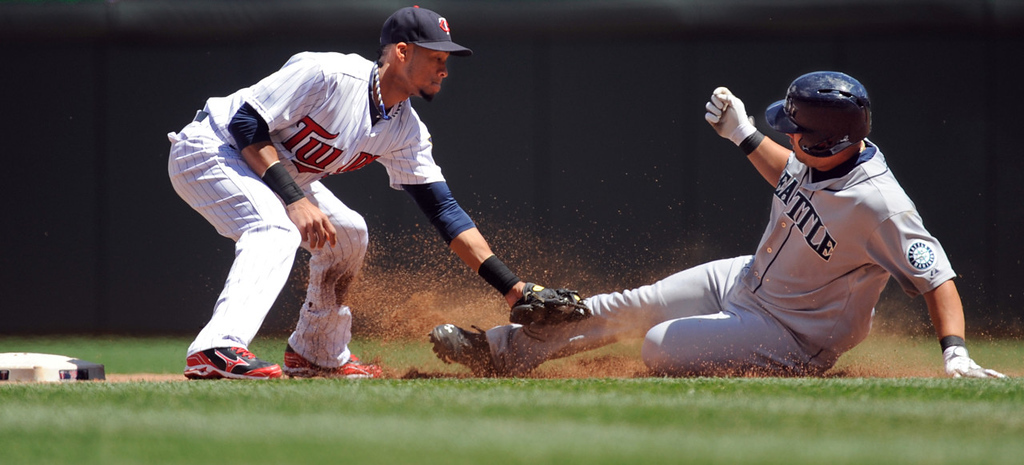 . Twins shortstop Pedro Florimon, left, tags out Seattle\'s Kendrys Morales after Morales tried to stretch his single to deep right field during the fourth inning. (AP Photo/Craig Lassig)