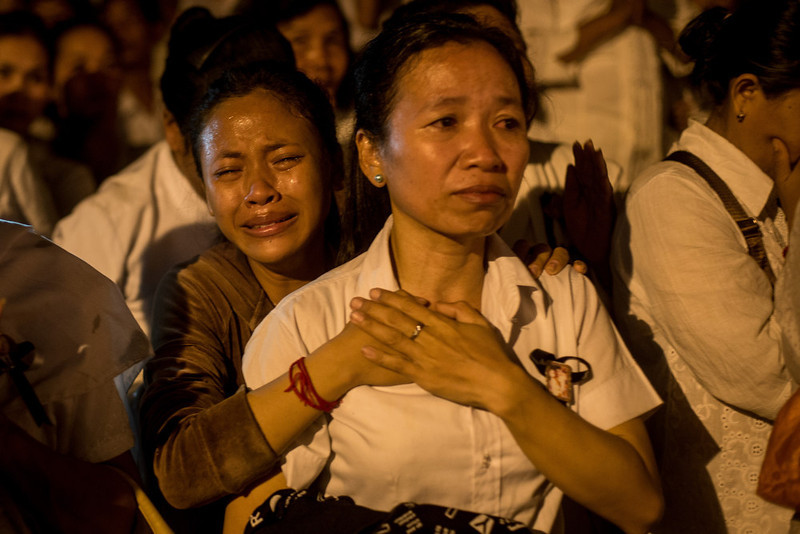 . Women grieve on the street after the the funeral fire was lit by King Norodom Sihamoni son of the late former King Norodom Sihanouk, and his mother, Queen Norodom Monineath during the cremation ceremony on February 4, 2013 in Phnom Penh, Cambodia. The former King\'s cremation ceremony comes on the fourth day of a seven day royal funeral ceremony and nearly four months since his death in Beijing last October. Foreign leaders from 16 countries attended the cremation ceremony.  (Photo by Chris McGrath/Getty Images)