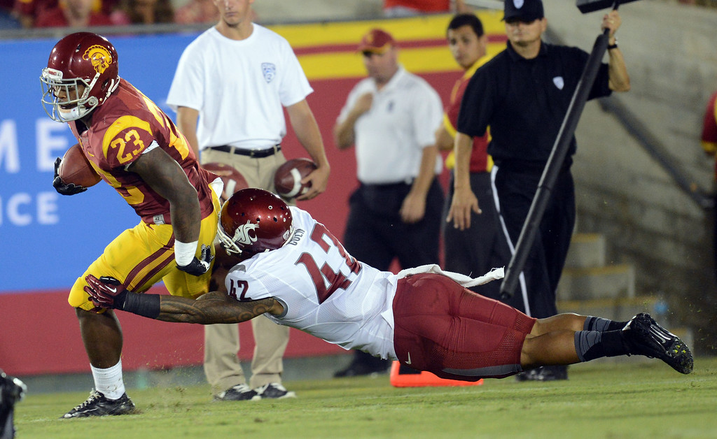 . USC\'s Tre Madden #23 escapes the tackle of \\Washington State\'s Cyrus Coen #42 during their game at the Los Angeles Memorial Coliseum  Saturday, September 7, 2013.  (Photo by Hans Gutknecht/Los Angeles Daily News)