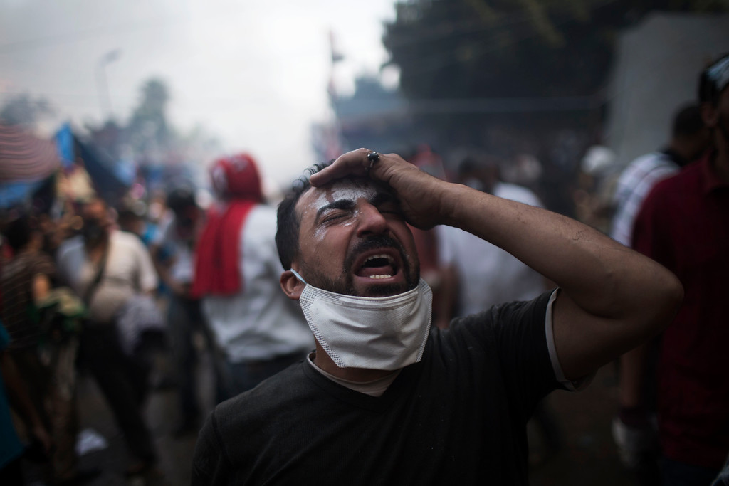 . A supporter of ousted Egyptian President Mohammed Morsi reacts during clashes with Egyptian security forces in Rabaah Al-Adawiya in Cairo\'s Nasr City district, Egypt, Wednesday, Aug. 14, 2013.  (AP Photo/Manu Brabo)