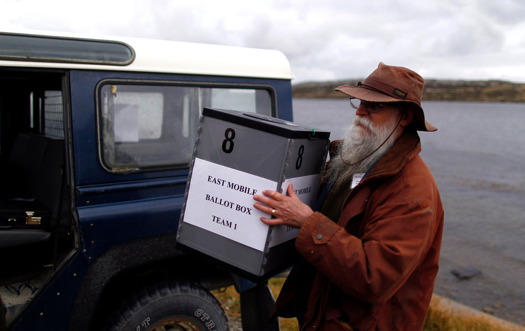 . Referendum volunteer Phil Middleton carries a mobile ballot box into a truck to take it to remote polling stations outside the Town Hall in Stanley, March 10, 2013. Voters in the remote British-ruled Falkland Islands held a referendum on their future today that seeks to challenge Argentina\'s increasingly vocal sovereignty claim.  REUTERS/Marcos Brindicci
