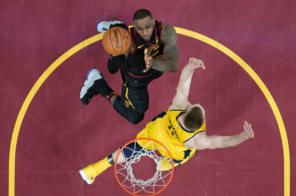. Cleveland Cavaliers\' LeBron James, top, drives against Indiana Pacers\' Domantas Sabonis, from Lithuania, in the first half of Game 1 of an NBA basketball first-round playoff series Sunday, April 15, 2018, in Cleveland. (AP Photo/Tony Dejak)