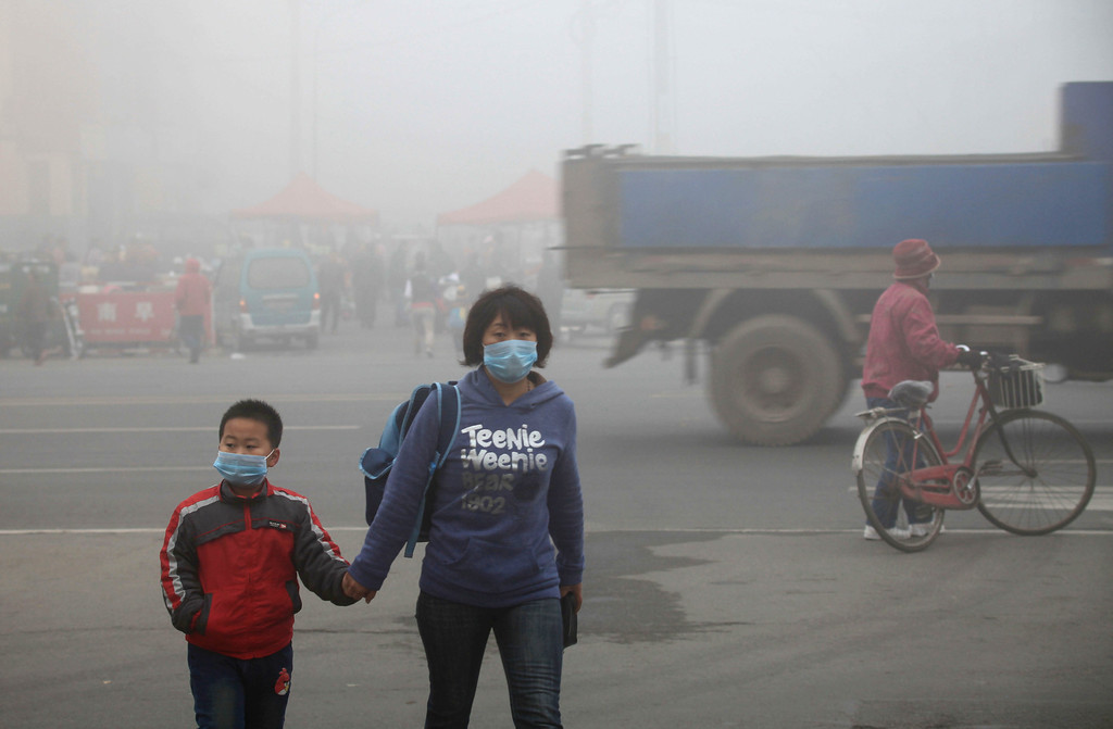 . A woman walks with her child on a street as schools were closed due to the heavy smog in Jilin, northeast China\'s Jilin province on October 22, 2013.    AFP PHOTOSTR/AFP/Getty Images