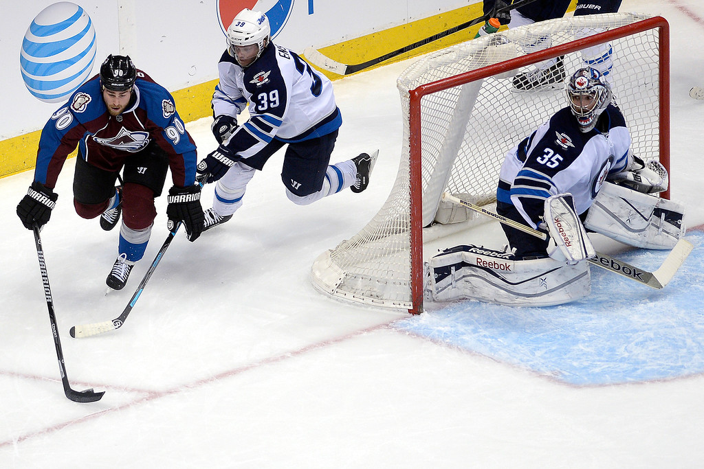 . Ryan O\'Reilly (90) of the Colorado Avalanche controls the puck as Tobias Enstrom (39) of the Winnipeg Jets defends and Al Montoya (35) mans the net during the first period. ( Photo by AAron Ontiveroz/The Denver Post)