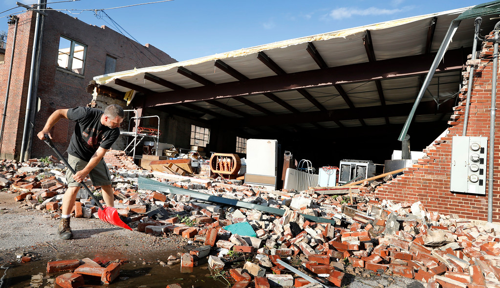 . Roy Schweinebart, of Marshalltown, Iowa, shovels bricks from a tornado-damaged building near Main Street, Thursday, July 19, 2018, in Marshalltown, Iowa. Several buildings were damaged by a tornado in the main business district in town including the historic courthouse. (AP Photo/Charlie Neibergall)