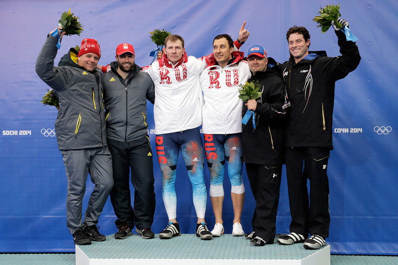 . Silver medalists Beat Hefti and Alex Baumann of Switzerland team 1, gold medalists Alexander Zubkov and Alexey Voevoda of Russia team 1 and bronze medalists Steven Holcomb and Steven Langton of the United States team 1 celebrate during the flower ceremony for the Men\'s Two-Man Bobsleigh on Day 10 of the Sochi 2014 Winter Olympics at Sliding Center Sanki on February 17, 2014 in Sochi, Russia.  (Photo by Adam Pretty/Getty Images)