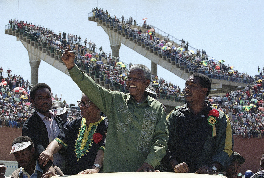 . African National Congress President Nelson Mandela, center, waves to supporters on his arrival at an election rally and Sharpville Day Commemoration Monday, March 21, 1994 in Mabopane, North of Pretoria in Bophuthatswana homeland. Monday is the 34th anniversary of the Sharpeville massacre in which 69 protesters were shot and killed by police in 1964. (AP Photo/Joao Silva)