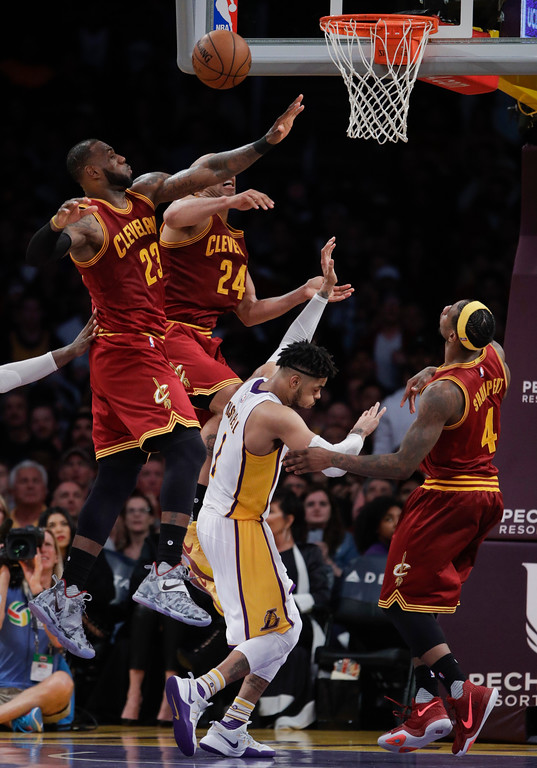 . Los Angeles Lakers\' D\'Angelo Russell, center, is defended by Cleveland Cavaliers\' LeBron James, top left, Richard Jefferson and Iman Shumpert, right, during the second half of an NBA basketball game Sunday, March 19, 2017, in Los Angeles. The Cavaliers won 125-120. (AP Photo/Jae C. Hong)