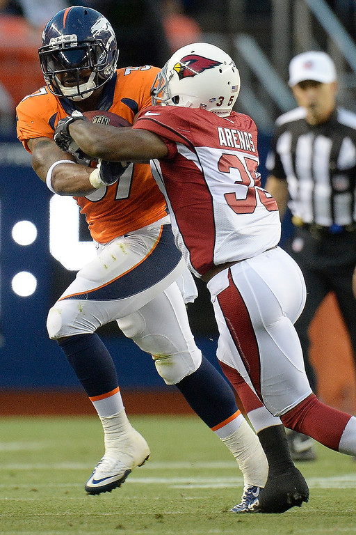 . Denver Broncos running back Jeremiah Johnson (37) stiff arms Arizona Cardinals cornerback Javier Arenas (35)during the first half on August 29, 2013 at Sports Authority Field at Mile High. The Denver Broncos hosted the Arizona Cardinals in the final game of the preseason. (Photo by John Leyba/The Denver Post)