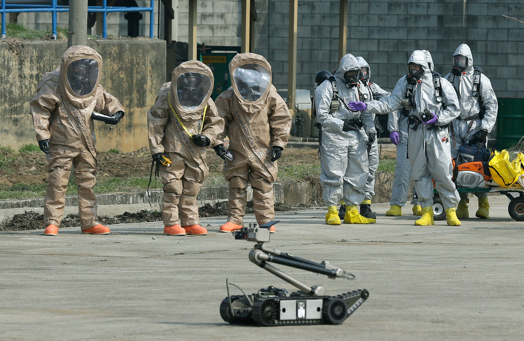 """. Soldiers of the U.S. Army 23rd chemical battalion, wearing anti-chemical suits, watch a bomb disposal robot during a demonstration of their equipment at a ceremony to recognize the battalion\'s official return to the 2nd Infantry Division based in South Korea at Camp Stanley in Uijeongbu, north of Seoul, Thursday, April 4, 2013. The 23rd chemical battalion left South Korea in 2004 and returned with some 350 soldiers in Jan. 2013. The battalion will provide nuclear, biological and chemical detection, equipment decontamination and consequence management assistance to support the U.S. and South Korean military forces. North Korea warned Thursday that its military has been cleared to attack the U.S. using \""""smaller, lighter and diversified\"""" nuclear weapons, while the U.S. said it will strengthen regional protection by deploying a missile defense system to Guam. (AP Photo/Lee Jin-man)"""