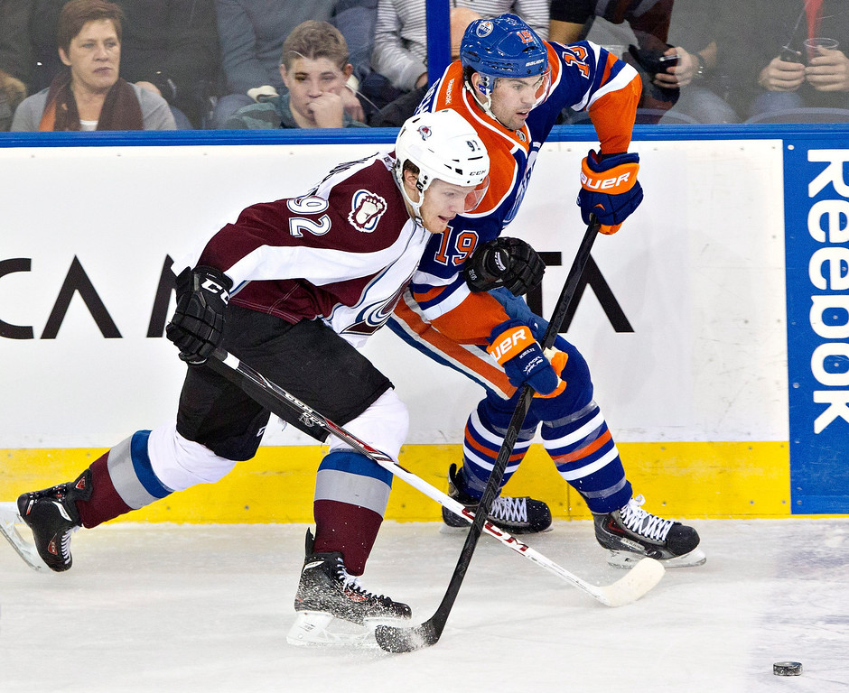 . Colorado Avalanche\'s Gabriel Landeskog (92) and Edmonton Oilers\' Justin Schultz (19) battle for the puck during second-period NHL hockey game action in Edmonton, Alberta, Thursday, Dec. 5, 2013. (AP Photo/The Canadian Press, Jason Franson)