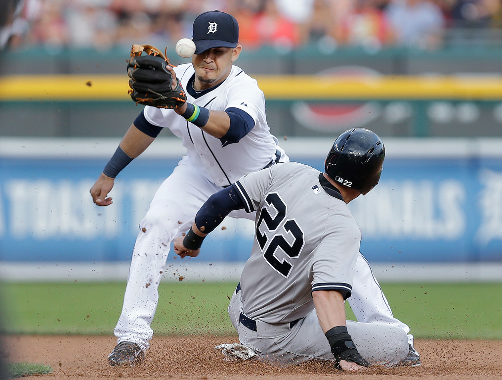 . Detroit Tigers shortstop Eugenio Suarez, left, cannot handle the throw as New York Yankees\' Jacoby Ellsbury (22) steals second base in the first inning of a baseball game in Detroit, Wednesday, Aug. 27, 2014. (AP Photo/Paul Sancya)