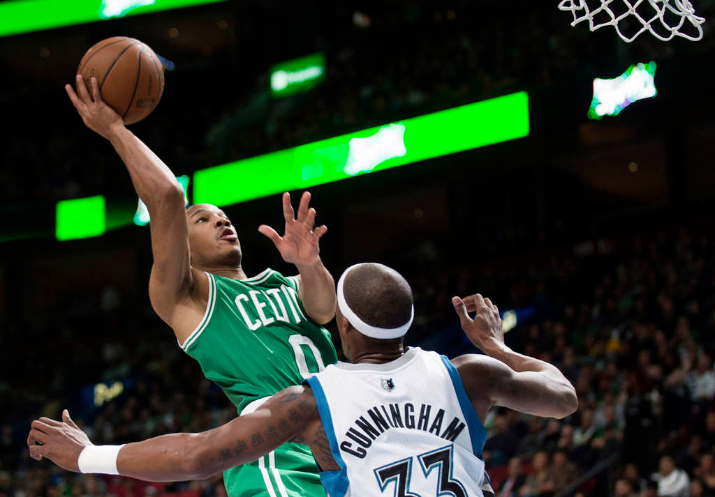 . Boston Celtics\' Avery Bradley, left, takes a shot on net as Minnesota Timberwolves\' Dante Cunningham defends during the second quarter. (AP Photo/The Canadian Press, Graham Hughes)
