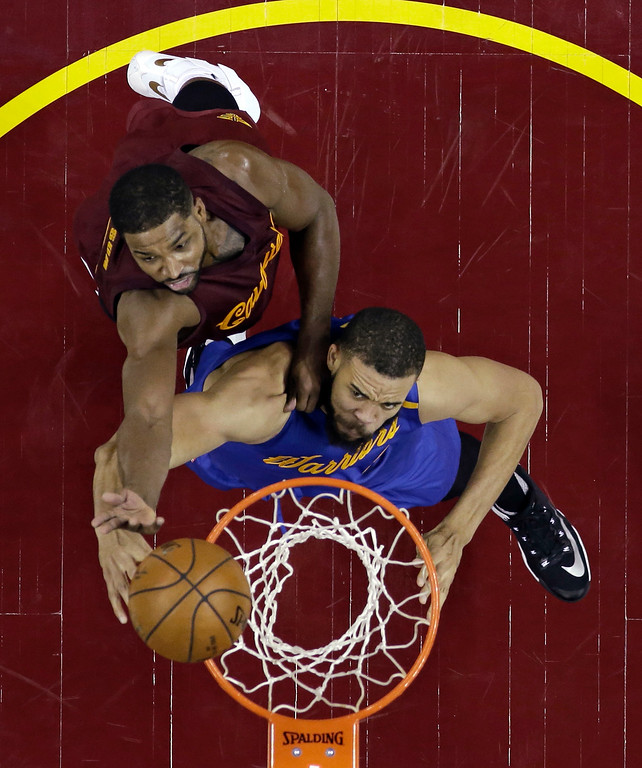 . Golden State Warriors\' JaVale McGee, bottom, drives to the basket against Cleveland Cavaliers\' Tristan Thompson in the second half of an NBA basketball game, Sunday, Dec. 25, 2016, in Cleveland. The Cavaliers won 109-108. (AP Photo/Tony Dejak)