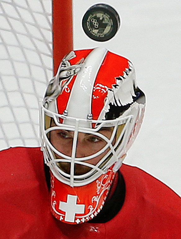 . Switzerland goaltender Reto Berra looks for the rebound against Sweden in the second period of a men\'s ice hockey game at the 2014 Winter Olympics, Friday, Feb. 14, 2014, in Sochi, Russia. (AP Photo/Julio Cortez)