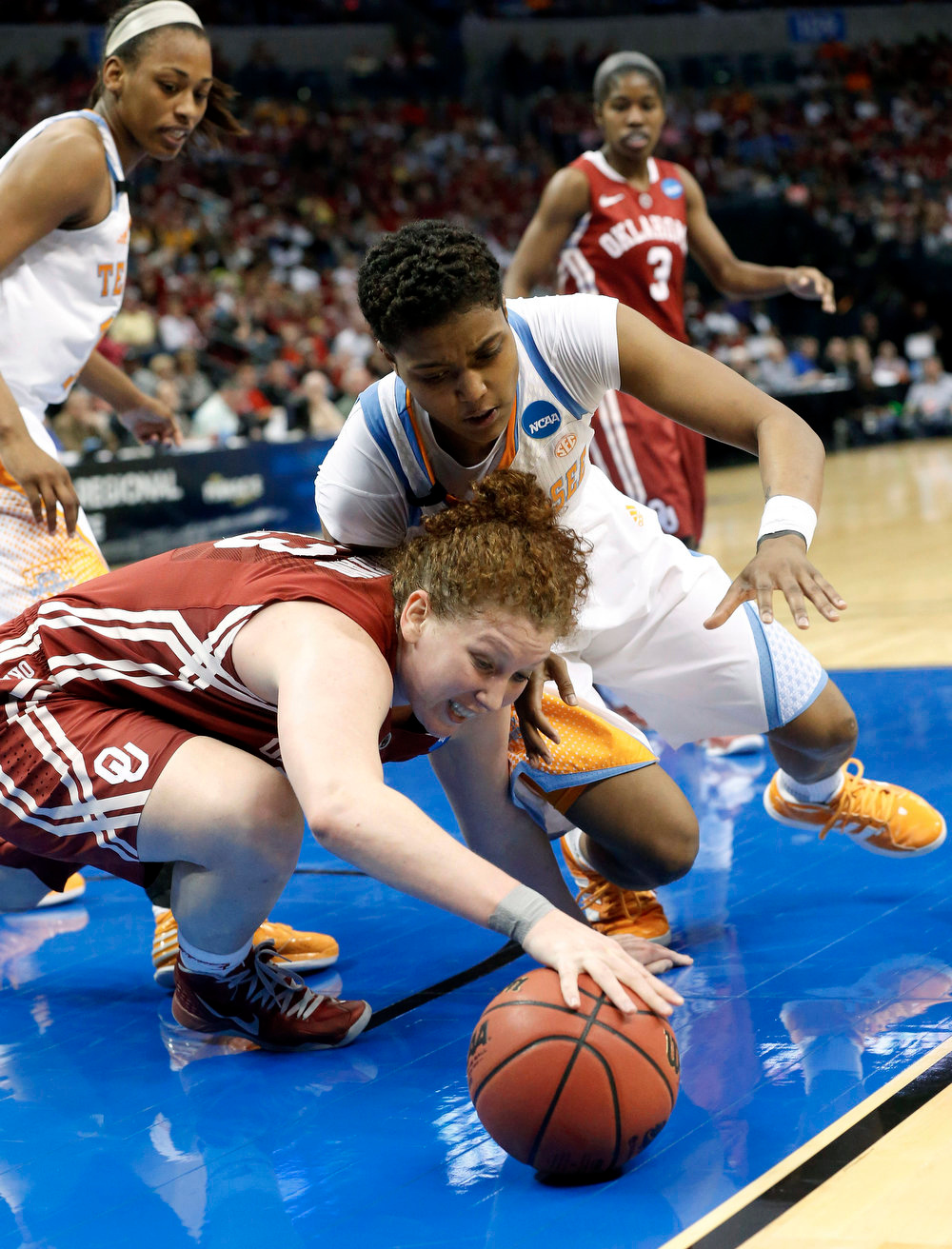 Description of . Oklahoma forward Joanna McFarland, left, and Tennessee guard Kamiko Williams, right, reach for the ball in the second half of a regional semifinal game in the women's NCAA college basketball tournament in Oklahoma City, Sunday, March 31, 2013. Tennessee won 74-59. (AP Photo/Sue Ogrocki)