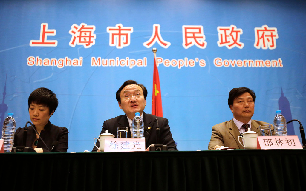 . Xu Jianguang, director-general and deputy secretary of the Communist Party of China Committee of Shanghai Municipal Health Bureau, speaks as Wu Fan, left, chief doctor and director-general of Shanghai Municipal Center for Disease Control, and Agricultural Committee Deputy Director Shao Linchu, right, listen during a press conference in Shanghai, China, Friday, April 5, 2013. China announced a sixth death from a new bird flu strain Friday, while authorities carried out the slaughter of all poultry at a Shanghai market where the virus was detected in pigeons being sold for meat. (AP Photo/Eugene Hoshiko)