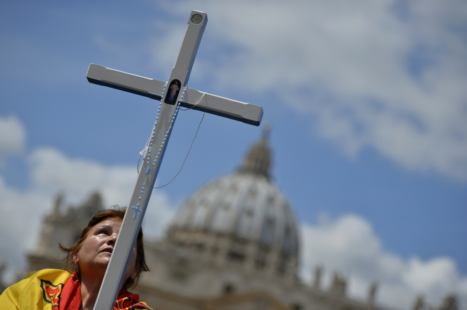 . A woman holds a cross on St Peter\'s square on April 26, 2014 at the Vatican a day before the canonisation of Popes John XXIII and John Paul II. Popes John Paul II and John XXIII will join the roster of saints at a historic Vatican ceremony on Sunday seen as an attempt to unite conservatives and reformists, with some 800,000 pilgrims expected in Rome. The double canonisation of two of modern-day Catholicism\'s most influential figures will be presided over by Pope Francis and may be attended by his elderly predecessor Benedict XVI, bringing two living pontiffs together to celebrate two deceased predecessors. (ANDREAS SOLARO/AFP/Getty Images)