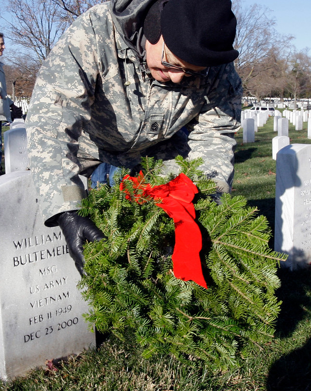 . Army Command Sgt. Maj. Fritz Bultemeyer of Decatur, Ind., places a wreath as the graves of his cousin as part of Wreaths Across America at Arlington National Cemetery in Arlington, Va., Saturday, Dec. 12, 2009. More than 16,000 wreaths were placed at graves throughout the cemetery. (AP Photo/Alex Brandon)