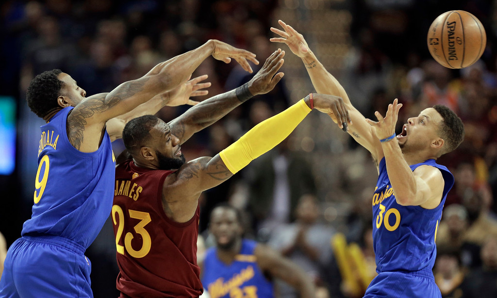 . Cleveland Cavaliers\' LeBron James (23) passes over Golden State Warriors\' Stephen Curry (30) as Andre Iguodala (9) defends in the second half of an NBA basketball game, Sunday, Dec. 25, 2016, in Cleveland. The Cavaliers won 109-108. (AP Photo/Tony Dejak)